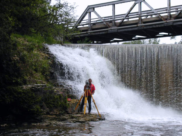 A man taking a topographical surveys by a waterfall