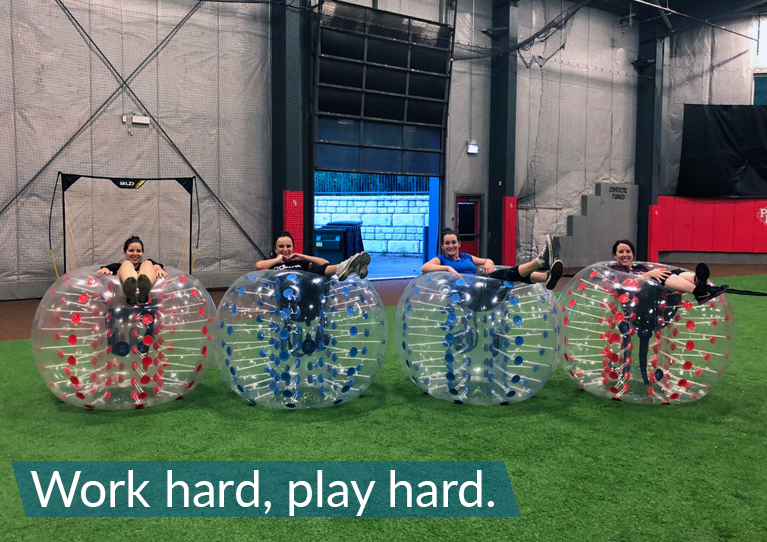 Coworkers playing bubble soccer